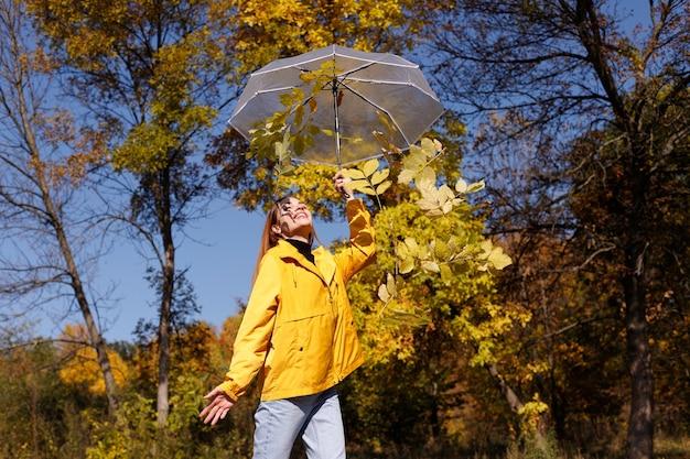 明るい天気の黄色の葉の前に紅葉と透明な傘を持つ感情的な女性