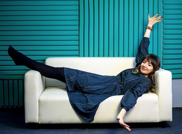 Эмоциональная молодая привлекательная женщина лежит на светлом диване счастливая и радостная, экспрессия и эмоции. перерыв на работе.