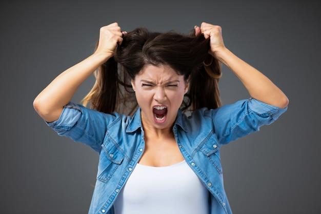 캐주얼 한 옷을 입은 감정적으로 화난 여성이 비명을 지르고 회색 벽 앞에서 머리카락을 꺼냅니다.