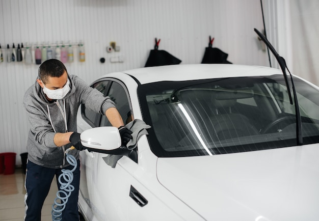 Сотрудник дует и вытирает машину после мытья. автомойка.
