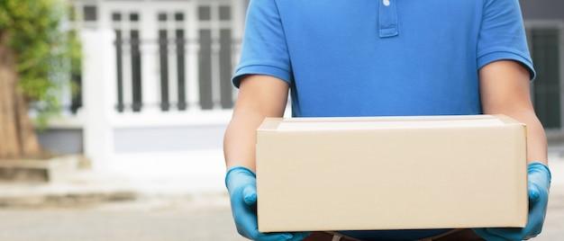 箱を持った従業員がお客様の家に商品を届けています。