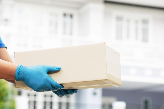 상자를 들고 있는 직원이 집으로 고객에게 제품을 배달하고 있습니다.