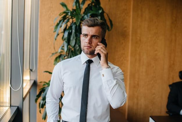 Сотрудник в офисе стоит возле окна. финансов