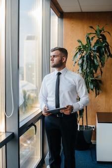 Сотрудник в офисе стоит возле окна
