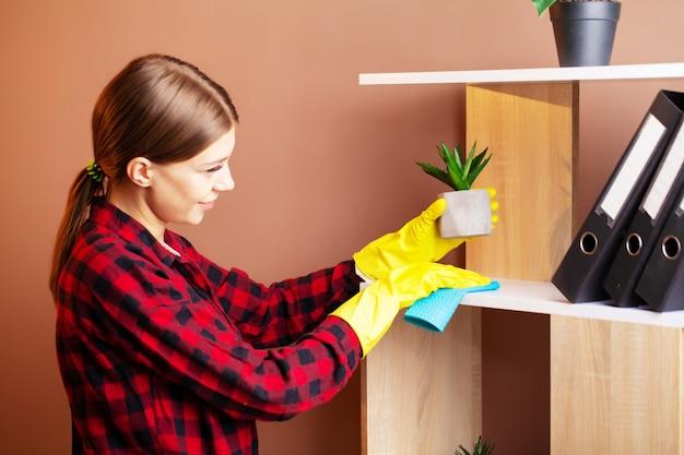 Сотрудник клининговой компании вытирает пыль с растений