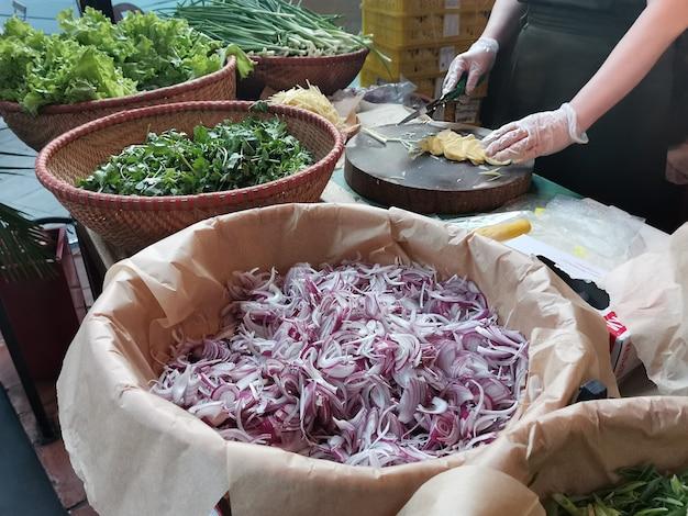 길거리 카페 직원이 포보스 프를 만들기위한 재료를 준비합니다. 베트남 카페에서 생강 슬라이스. 큰 바구니에 다진 붉은 양파와 허브. 전통적인 아시아 음식.