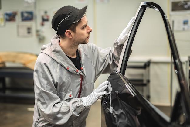 Сотрудник цеха покраски кузова проверяет качество