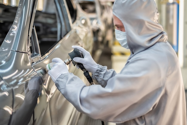 Сотрудник цеха покраски кузовов автомобилей в белых перчатках шлифует окрашенную поверхность.