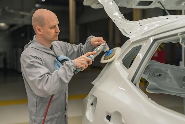 車体塗装店の従業員が塗装面を磨く