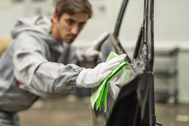 Сотрудник малярного цеха автозавода проводит обучение по подготовке бамперов к покраске.