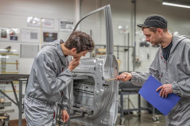 車体塗装工場の品質部門の従業員が品質をチェックし、欠陥を指摘