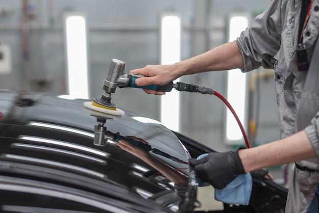 Сотрудник полирует окрашенную поверхность автомобиля