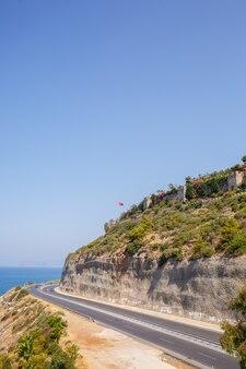 晴れた夏の日には、息を呑むような美しい海岸線に沿って空のアスファルト道路が曲がりくねっています。澄んだ青い空と穏やかな地中海を見下ろす海岸道路の壮大なショット。