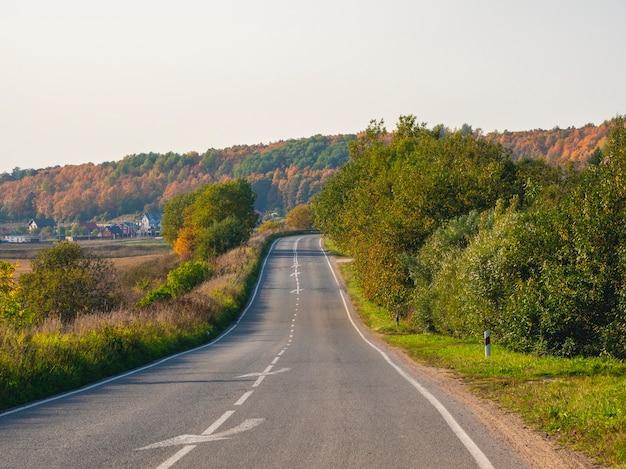 コテージのある美しい秋の丘に囲まれた、空っぽの秋の高速道路の田舎道。道路を急に曲がる。