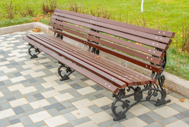 Пустая скамейка в городском парке осенью