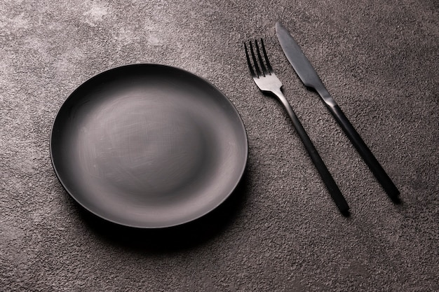 Пустая черная тарелка, вилка и ложка на темном фоне. минималистичный натюрморт
