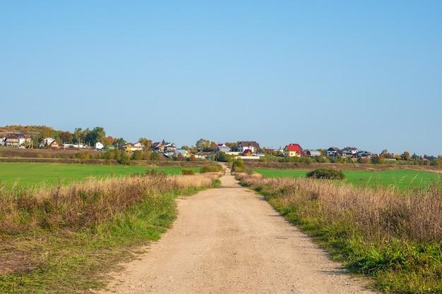 오두막이있는 언덕으로가는 빈 비포장 시골 길. 러시아.