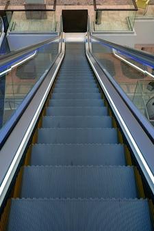 현대적인 쇼핑 센터 내부의 빈 에스컬레이터 계단이 이어집니다. 쇼핑몰에서 인터넷으로 이동하는 고객의 개념. 프리미엄 사진