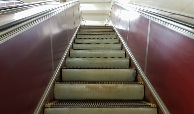 Пустой эскалатор без людей на станции метро красной линии киевского метро. крупным планом металлические ступени эскалатора, движущиеся снизу вверх.