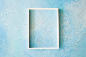 An empty frame with white border on blue painted wall