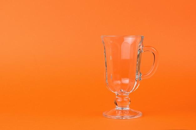 オレンジ色の背景に空のガラスコーヒーグラス。