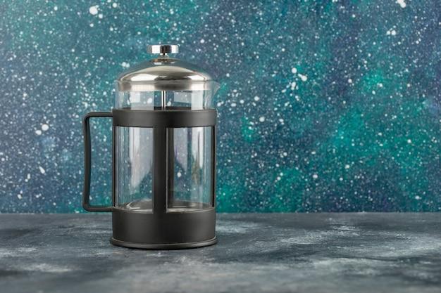 Пустой стеклянный чайник на яркой поверхности.