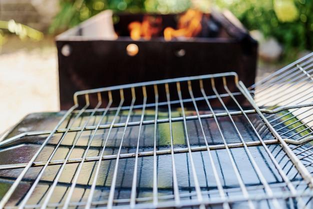 Пустая решетка-гриль на фоне мангала, приготовленная для выкладывания на нее мяса или овощей. отдых на природе.