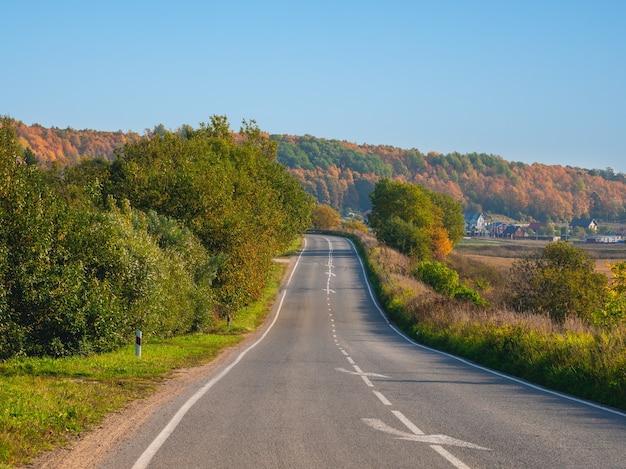 コテージのある美しい秋の丘に囲まれた空の高速道路の田舎道。道路を急に曲がる。