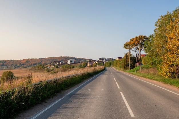 コテージのある美しい秋の丘に囲まれた空の高速道路の田舎道。