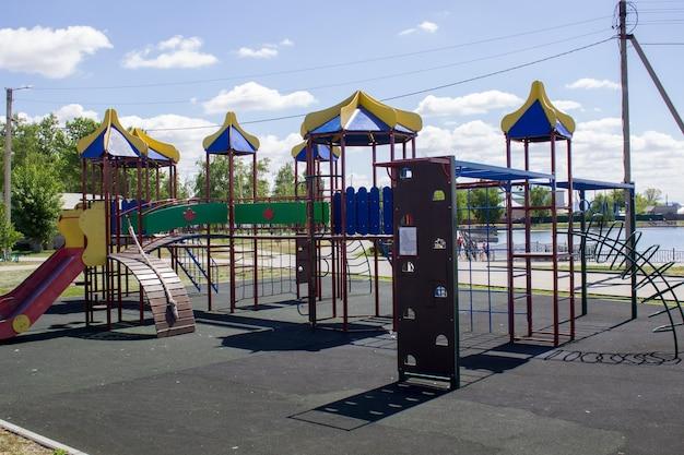 Пустая разноцветная и безопасная детская площадка с горкой в городском парке.