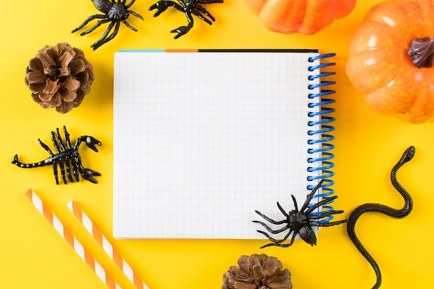 Пустой блокнот для текста в окружении тыкв, паучьих фигурок змей на желтом фоне ч ...
