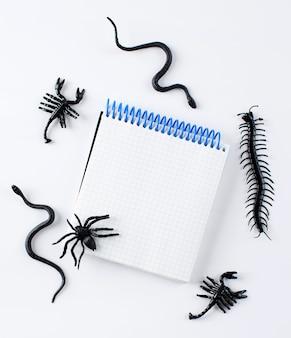 Пустой блокнот для текста в окружении фигур пауков змей на белом фоне хэллоуин с ...