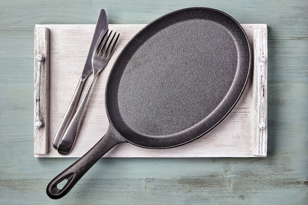 Пустая овальная чугунная сковорода на деревянном подносе на голубом кухонном столе. макет меню ресторана