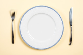 An empty plate between the fork and butter knife on beige backdrop