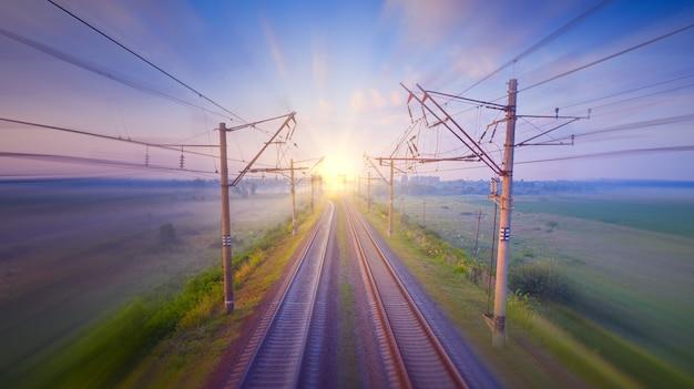 夜明けの空の鉄道、長いシャッタースピードで撃たれた旅客列車からの光の道。コンセプト、旅行、交通機関。