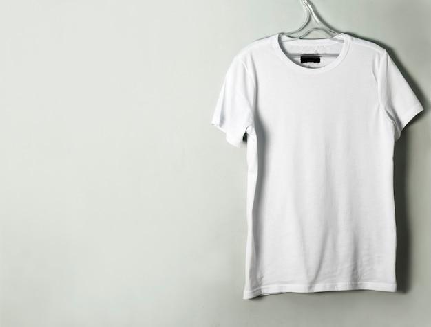 빈 티셔츠가 공간의 사본과 함께 벽에 걸려 있습니다.