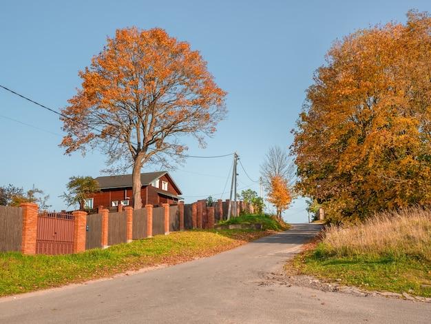 柵の後ろに家がある空の村の秋の道。