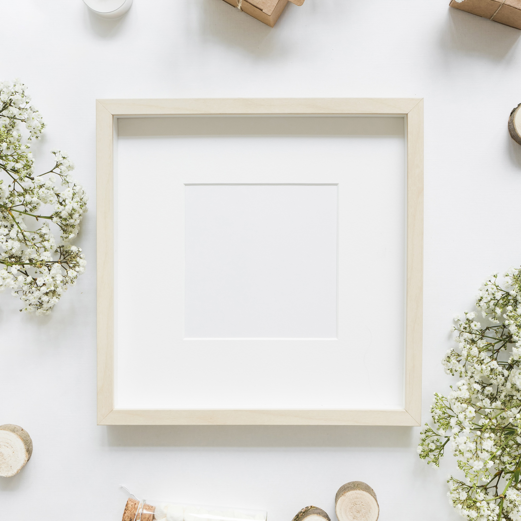 An empty white frame surrounded with flowers and gift boxes