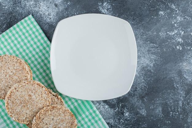 대리석 표면에 바삭한 쌀 빵과 함께 빈 흰색 접시.