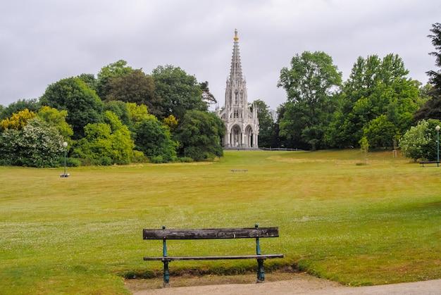 Пустая деревянная скамья перед полем и церковью, брюссель, бельгия