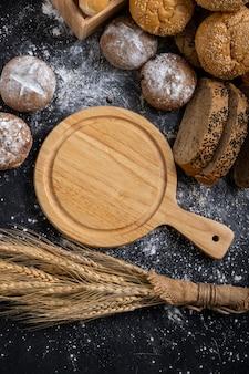 空の木製まな板とパンとテーブルの上の小麦