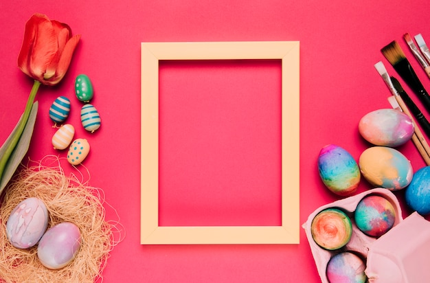 Пустая желтая рамка с красочными пасхальными яйцами; кисти для рисования; тюльпан на розовом фоне