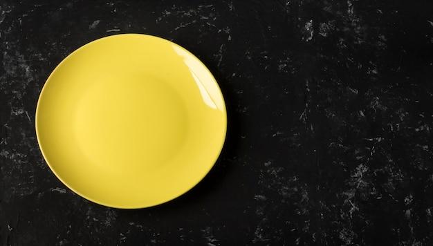 Пустая желтая тарелка на черном текстурированном фоне с копией пространства.