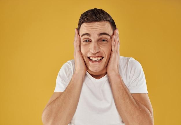 白いtシャツを着たエネルギッシュな男が黄色の背景に彼の手で彼の頭に触れます