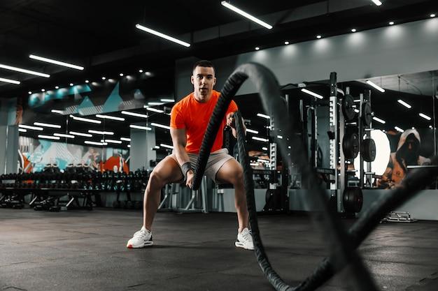 エネルギッシュなスポーツマンが、黒い背景と大きな鏡のある屋内ジムで、バトルロープを使った有酸素運動のクロスフィットトレーニングを行っています。