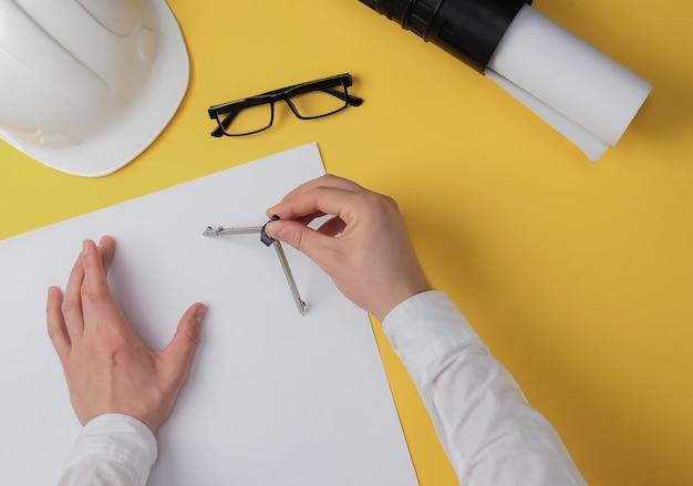 Инженер рисует фигуру на листе бумаги среди рабочего пространства на желтом фоне с компасом. вид сверху. строитель, прораб