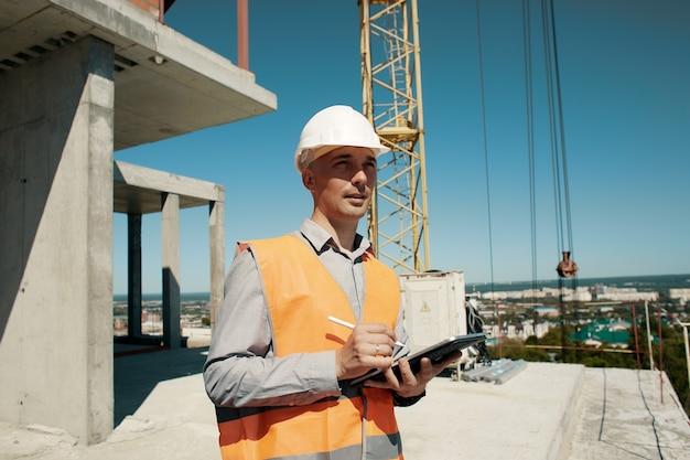Инженер в оранжевом жилете и белом шлеме строительного контролера с планшетом в руках проводит осмотр строительной площадки и башенного крана.