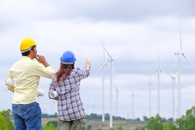 エンジニアは設計図を持って立ち、風力タービンプロジェクトを見て発電し、風向を確認します。
