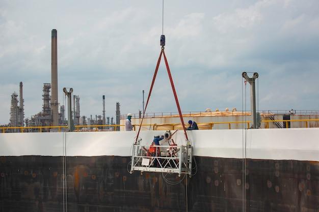 안전 유니폼과 안전 헬멧을 착용한 엔지니어 용접 탱크가 높이에서 크레인 붐 리프트 작업을 제어합니다.