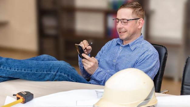 안경을 쓴 엔지니어가 작업대에 발을 던졌습니다. 전화로 좋은 소식이 보입니다. 온라인 회의. 라도스니 소식.